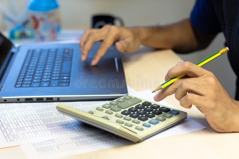 Nahaufnahme-Geschäftsmann, der Taschenrechner und conmputer Laptop für c verwendet stockbilder