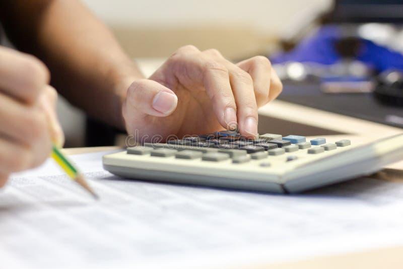 Nahaufnahme-Geschäftsmannbuchhaltung unter Verwendung des Taschenrechners für die Berechnung stockfotos