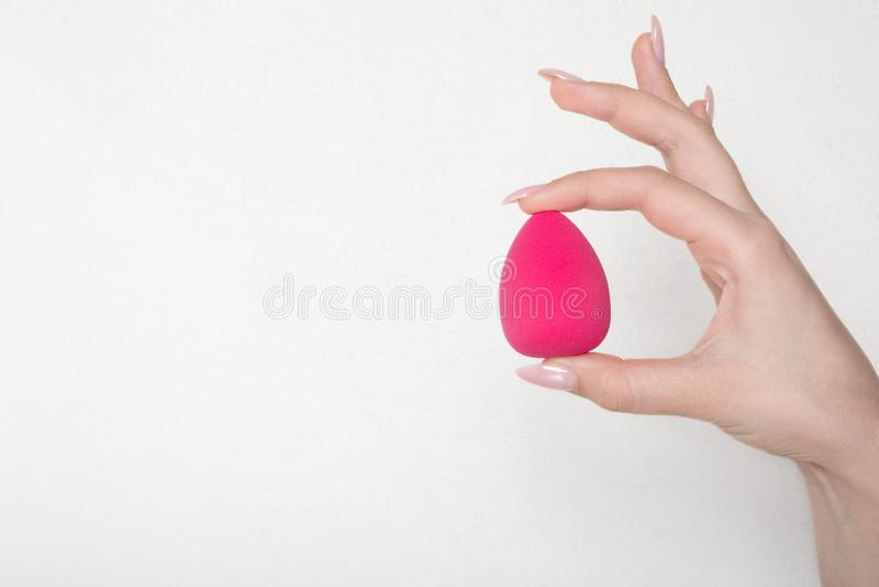 Nahaufnahme geschossen von der weiblichen Hand, die rosa Eischwamm über einem weißen Hintergrund hält Leerer Raum lizenzfreies stockfoto