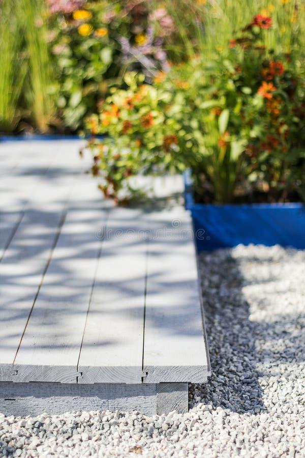 Nahaufnahme, hölzerne Terrasse und Blumenbeet, selektiver Fokus vertikal stockbild