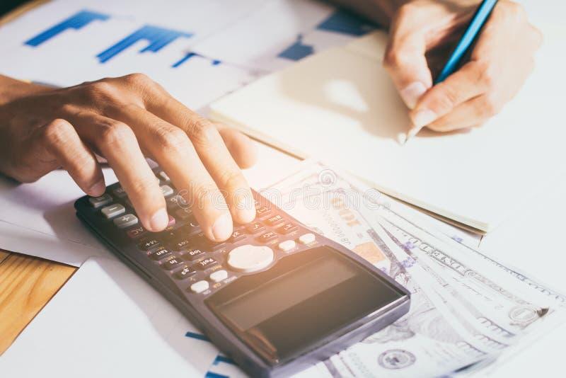 Nahaufnahme Hand des Gesch?fts- oder Kontoarbeitstaschenrechners, Gewinn oder Diagrammwirtschaft auf Hauptb?rotisch lizenzfreies stockbild