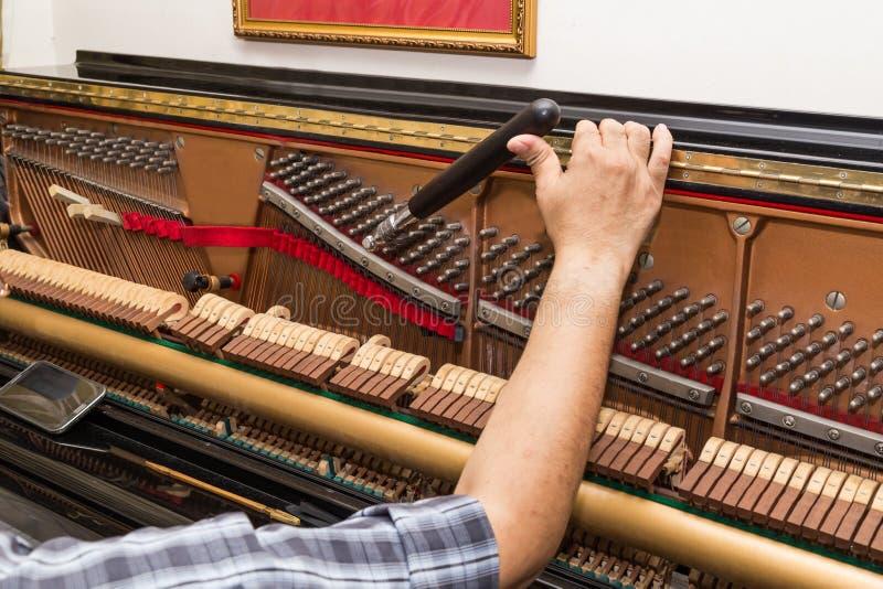 Nahaufnahme an Hand, die ein aufrechtes Klavier unter Verwendung des Hebels und der Werkzeuge abstimmt stockfoto