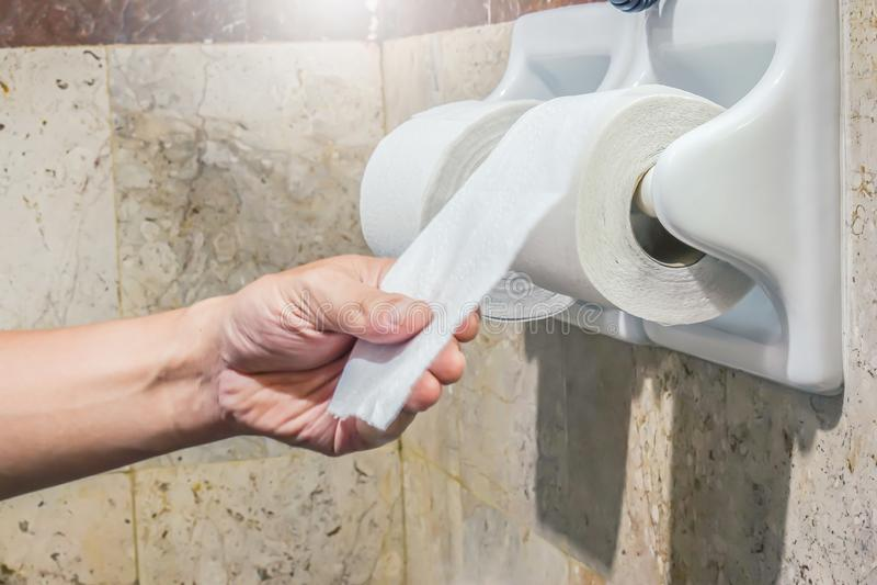 Nahaufnahme-Hand wählt ein weißes Toilettenpapier aus, das an der Wand im Badezimmer hängt stockbild