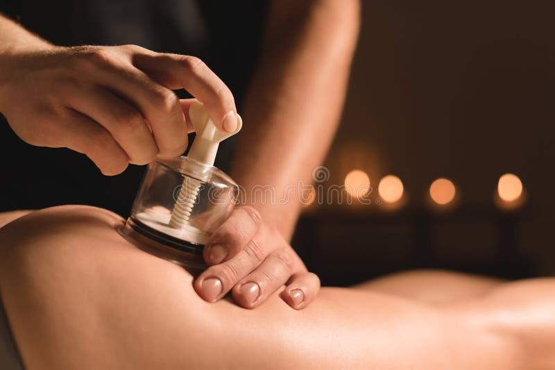 Nahaufnahme-Hardware Cosmetology Vakuummassageverfahren Männliche Hände installieren Vakuumbanken Nahaufnahme von AntiCellulite stockfoto