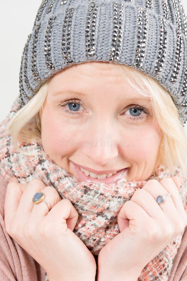 Nahaufnahme lächelnder blonder Dame Wearing Winter Beanie und Schal stockfotos
