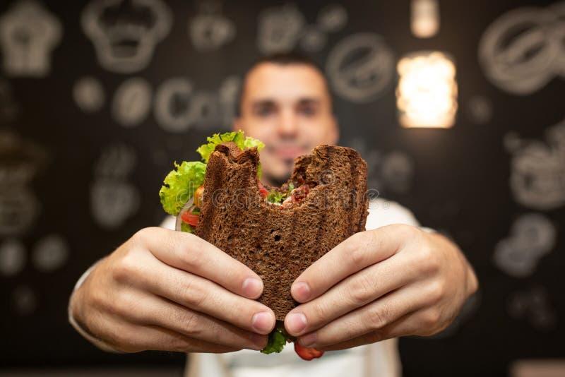 Nahaufnahme lustiges unscharfes protrait des gebissenen Sandwiches des jungen Mannes Griff durch seine zwei H?nde Sandwich im Fok stockfotos