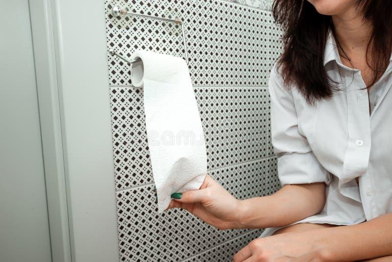 Nahaufnahme, Mädchen reißt Toilettenpapier beim Sitzen auf der Toilette auseinander stockfoto
