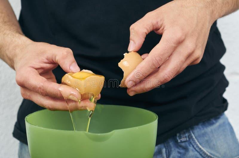 Nahaufnahme man& x27; s-Hände brechen das Ei und trennen das Weiß von t lizenzfreie stockfotografie
