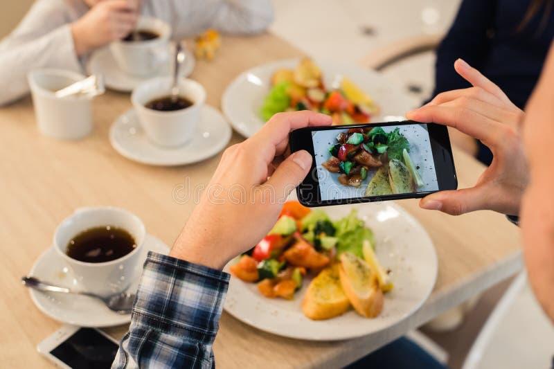 Nahaufnahme-Mann ` s übergibt das Machen des Fotos des Lebensmittels mit intelligentem Mobiltelefon stockfotografie