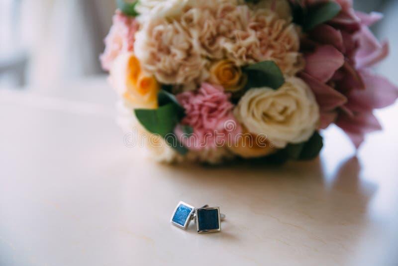 Nahaufnahme Manschettenknöpfe und ein Hochzeitsblumenstrauß auf einer weißen Tabelle Bekleidungszubehör für Geschäftsmann oder Br stockfotografie