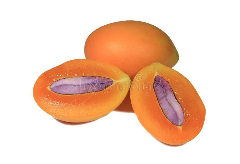 Nahaufnahme neue reife orange Farbder ganzen Frucht und -schnittes Marian Plumss zur Hälfte mit purpurrotem Samen stockfotografie