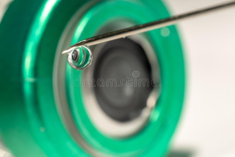 Nahaufnahme oder Makro der Spritzennadel mit einem Tropfen an der Spitze, Kappe einer Phiolenflasche im Hintergrund lizenzfreie stockfotos