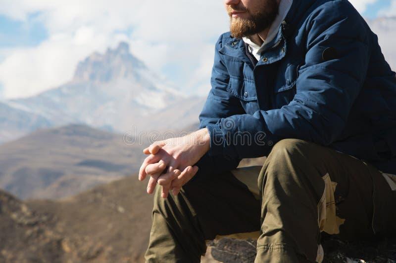 Nahaufnahme ohne einen sitzenden Hippie des Gesichtes auf einem Stein hoch in den Bergen vor dem hintergrund der epischen Felsen  stockfoto