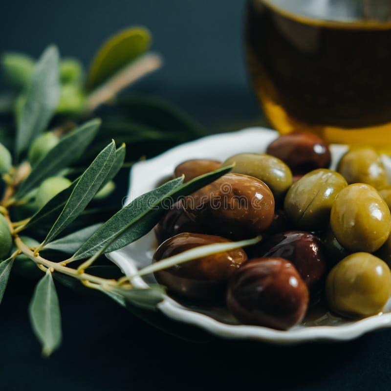 Nahaufnahme-organische Oliven, reines Öl und grüne Niederlassung auf schwarzem BAC lizenzfreies stockfoto