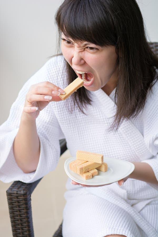 Nahaufnahme-Porträt der jungen hübschen Frau mit Raserei isst Oblate, s stockfoto