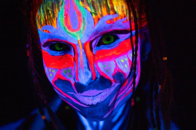 Nahaufnahme-Portr?t der jungen nackten bodyarted Frau in der blauen gl?henden ultravioletten Farbe und in den gelben Augenlinsen  lizenzfreie stockbilder