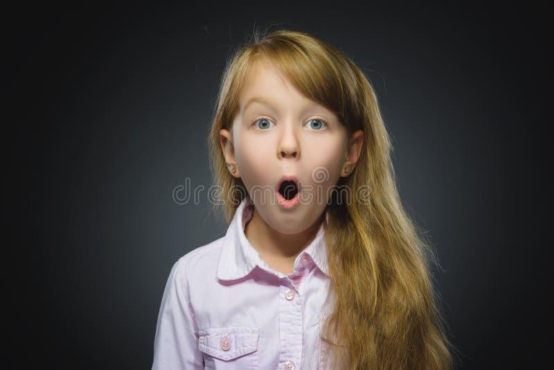 Nahaufnahme-Porträt der wundernden gehenden Überraschung des Mädchens auf grauem Hintergrund stockbilder