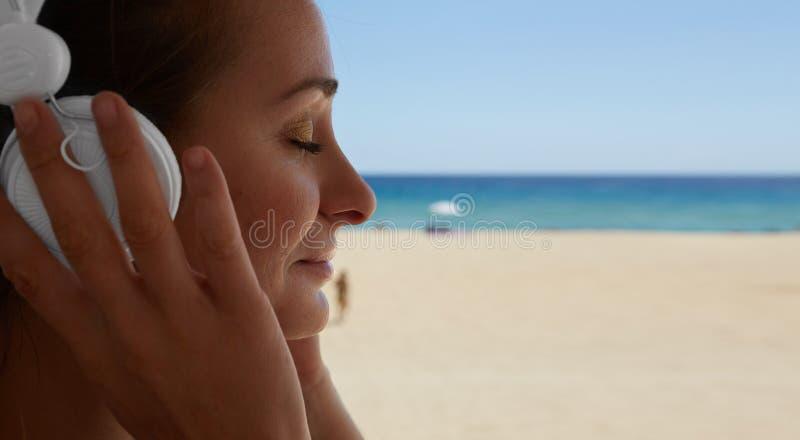 Nahaufnahme-Porträt-hübscher junge Frauen-hörender Musik-Spieler-Kopfhörer-Seestrand-Hintergrund Hübsches Mädchen genießen Audio stockbilder