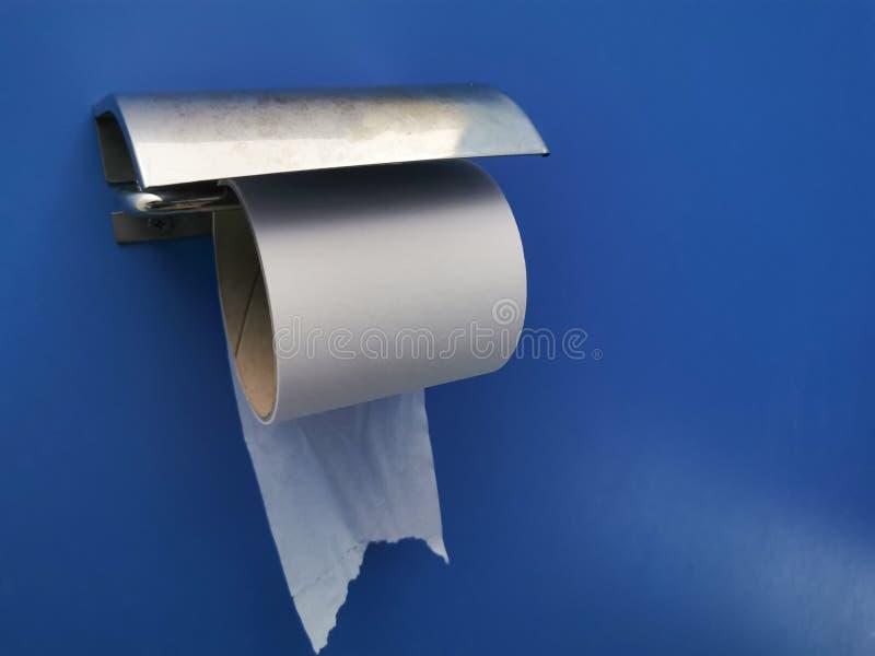 Nahaufnahme-Rolle des Toilettenpapiers oder des Gewebes auf blauer Wandfarbe stockbild