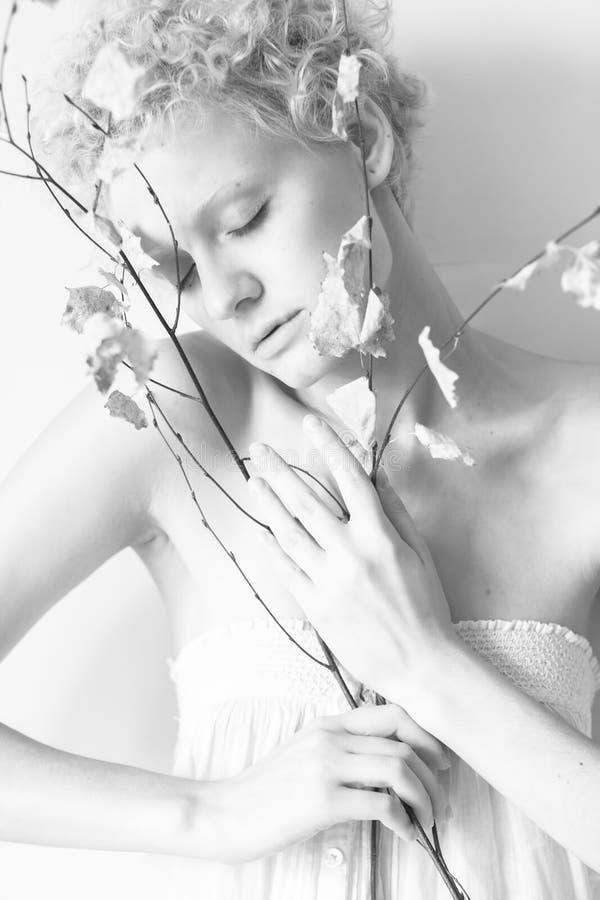 Nahaufnahme schön dünn mit Mädchenmodell des gelockten Haares mit einem trockenen Baumast lizenzfreies stockfoto
