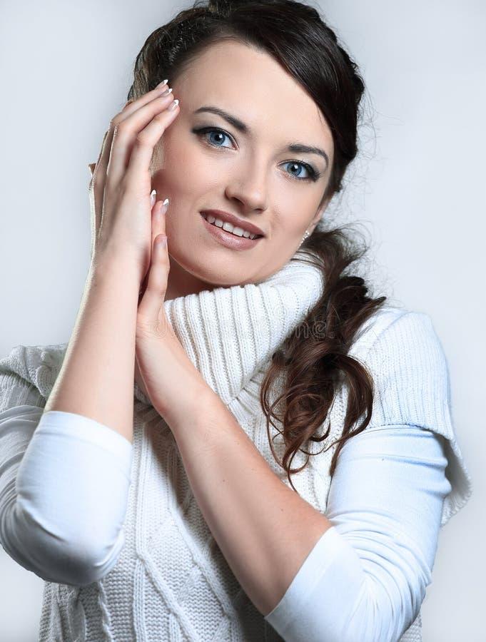 nahaufnahme schöne junge Frau in der weißen Strickjacke, die vor der Kamera aufwirft stockfotografie