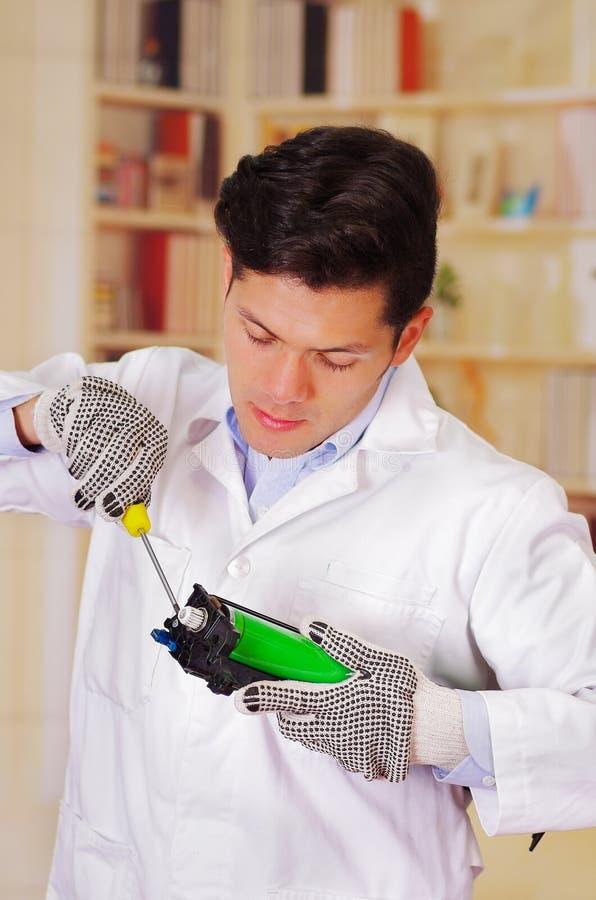 Nahaufnahme schoss den jungen männlichen Techniker, der einen Toner unter Verwendung eines Schraubenziehers repariert stockbild