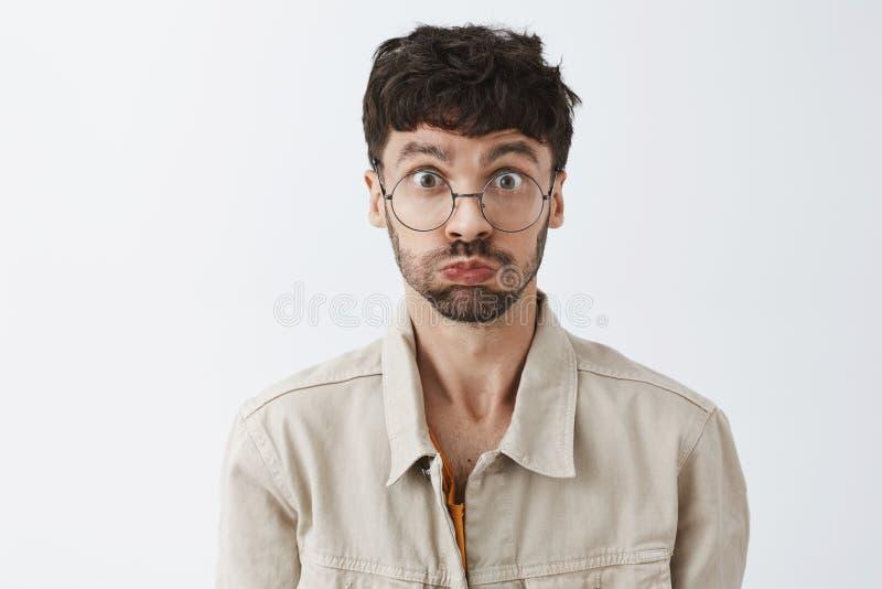 Nahaufnahme schoss vom dummen und spielerischen attraktiven jungen bärtigen Kerl mit dem dunklen Haar schmollend, Atem halten und lizenzfreie stockfotografie