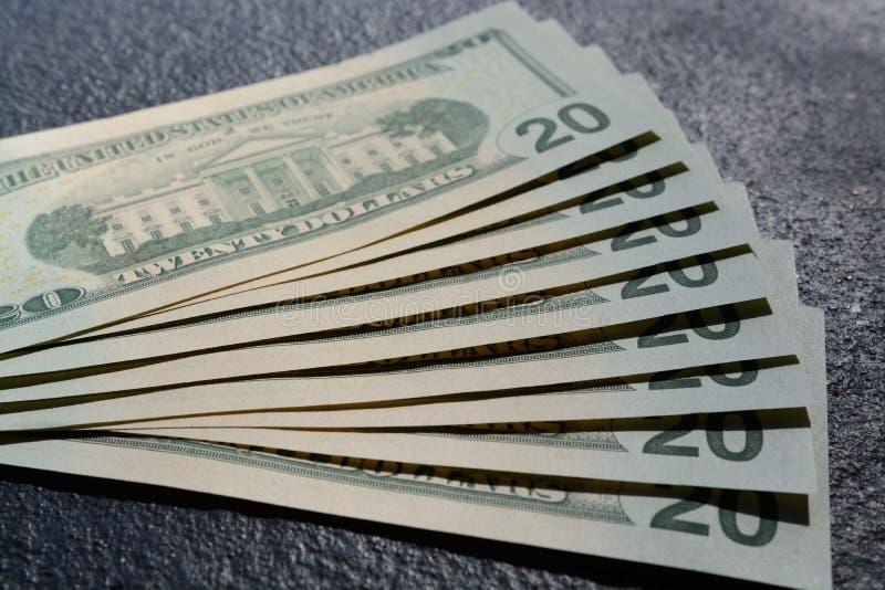 Nahaufnahme schoss von einem Stapel von zwanzig Dollar auf einem grauen konkreten Hintergrund lizenzfreie stockfotografie