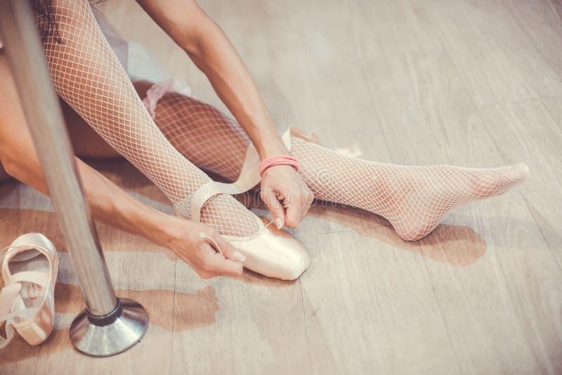 Nahaufnahme schoss von einer Ballerina, welche die Ballettschuhe entfernt, die auf dem Boden im Studio nahe dem Pfosten sitzen lizenzfreies stockbild