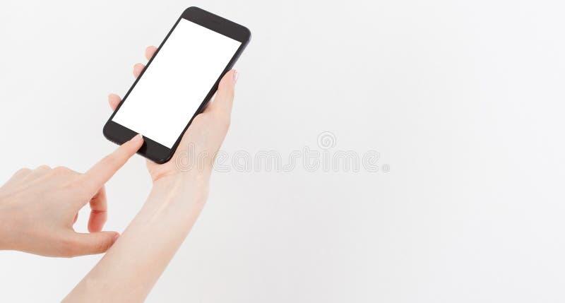 Nahaufnahme schoss von einer Frau, die am Handy auf weißem Hintergrund schreibt Leerer Bildschirm, zum es auf Ihre eigene Webseit stockfotografie