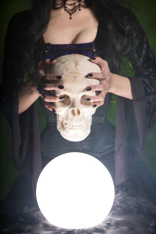 Nahaufnahme schoss von einer Hexe mit den langen Nägeln, die menschlichen Schädel halten stockfoto