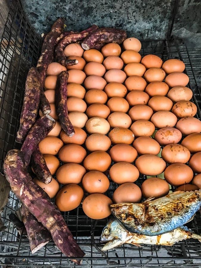 Nahaufnahme-traditionelles Thailand-Straßen-Lebensmittel: Gegrillt/briet Hühnereien, süße Wasserbrotwurzeln, Makrelenfische und M lizenzfreie stockfotos