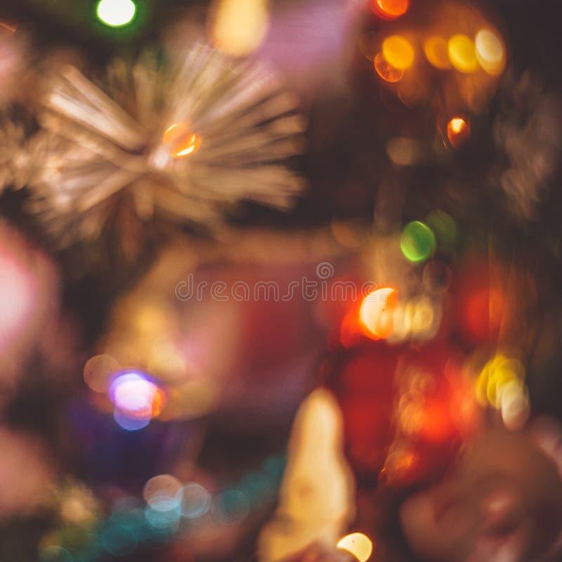 Nahaufnahme verwischte Fragment des Weihnachtsbaums mit Spielwaren, Lichtern von Gerland und Lametta Retro- Tonart, Fokus heraus lizenzfreies stockfoto