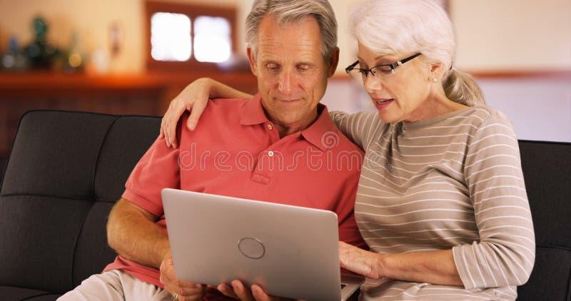 Nahaufnahme von älteren Paaren unter Verwendung des Laptops zu Hause lizenzfreie stockbilder
