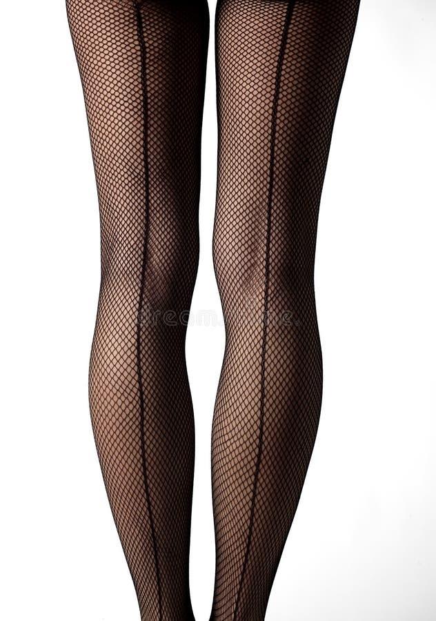 Nahaufnahme von Beinen mit Fischnetzstrümpfen und -Abwehrreihe lizenzfreies stockbild