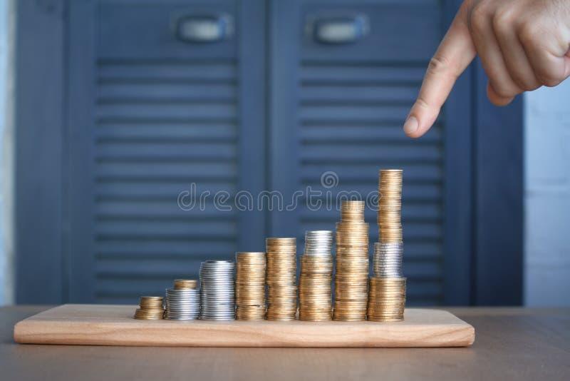 Nahaufnahme von a bemannt die Hand, die auf Spalten von mehrfarbigen Münzen der zunehmenden Höhe, des Konzeptes der Einsparung un lizenzfreie stockfotografie