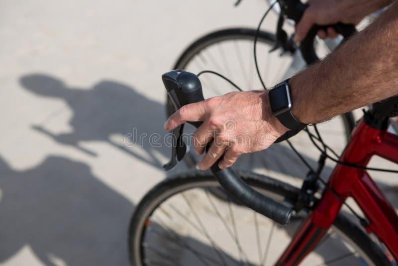 Nahaufnahme von bemannt Handtragendes smartwatch beim Fahren von Fahrrad stockfotos