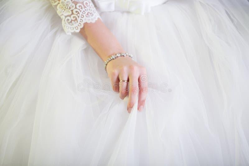 Nahaufnahme von Braut ` s Hand korrigiert den geschwollenen weißen Rock Hochzeits-Kleiderdetails lizenzfreies stockbild