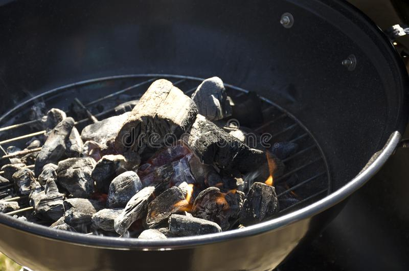 Nahaufnahme von brennenden Kohlen und von Holz auf einem Grillgitter lizenzfreie stockfotos