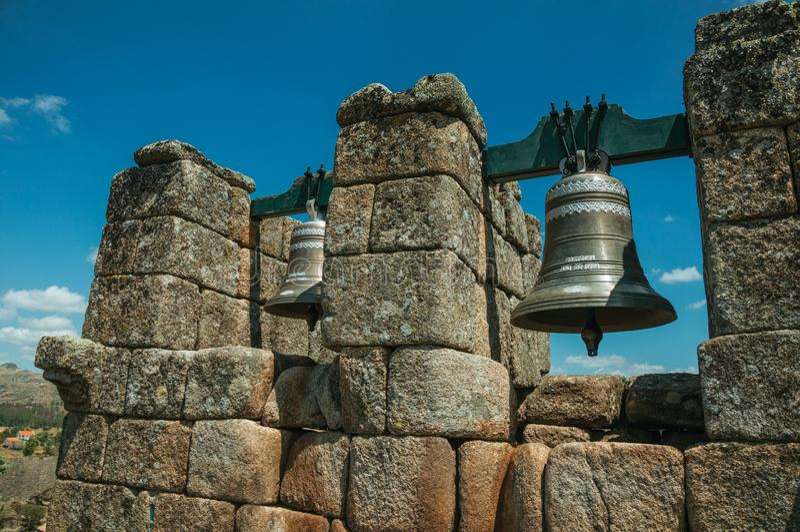 Nahaufnahme von Bronzeglocken auf Steinbacksteinmauer stockfotos