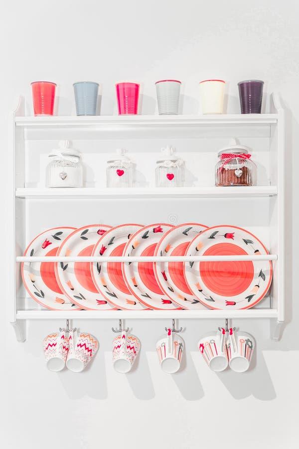 Nahaufnahme von bunten Platten und von Essgeschirr in einem Schrank auf Whit stockfoto
