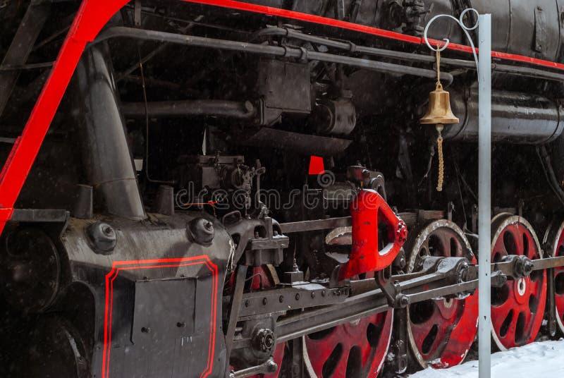 Nahaufnahme von Dampflokomotivrädern mit Stationsglocke stockbilder