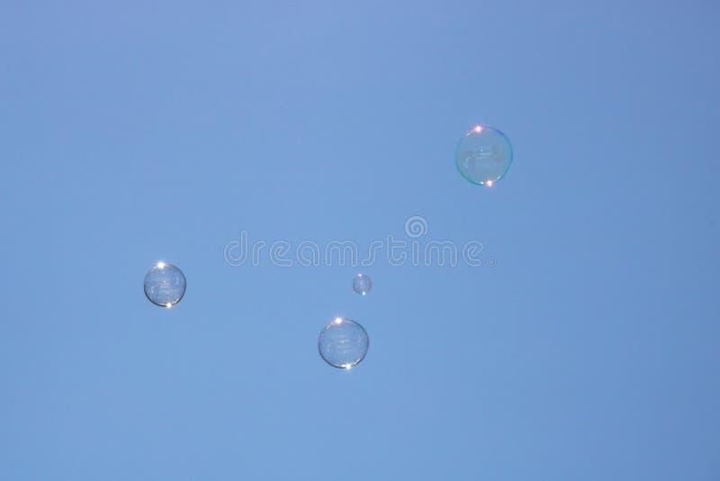 Nahaufnahme von den Blasen, die in Hintergrund des blauen Himmels schwimmen stockfoto