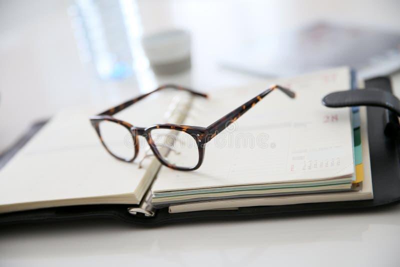 Nahaufnahme von den Brillen gelassen auf Tagesordnung lizenzfreies stockbild