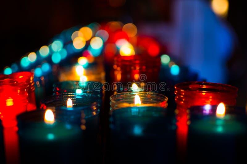 Nahaufnahme von den bunten Kerzen, die im Tunnel von Covadonga, Cangas de Onis, Asturien, Spanien brennen spirituality lizenzfreie stockbilder