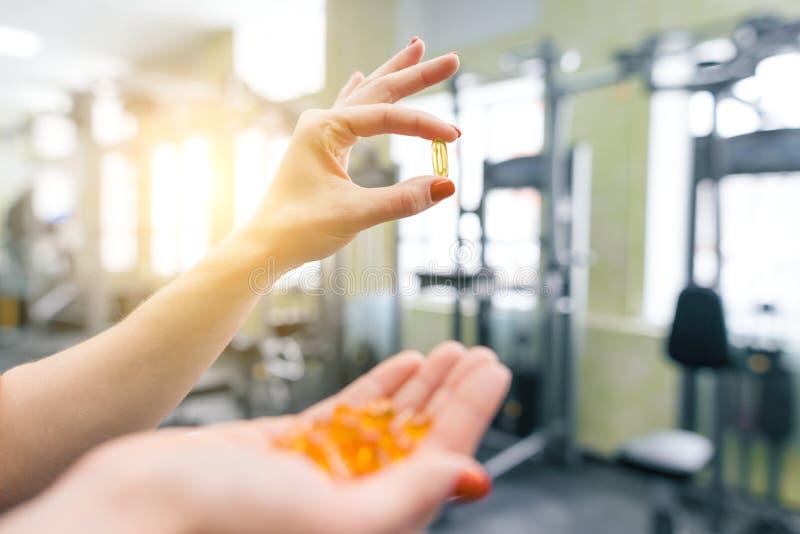 Nahaufnahme von den Eignungsfrauenhänden, die Kapsel omega-3, Turnhallenhintergrund des Vitamins e zeigen Gesunder Lebensstil, Me lizenzfreie stockfotografie