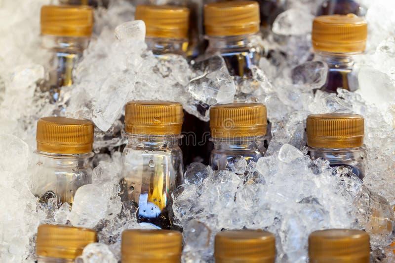 Nahaufnahme von den Flaschen, die kühl in den Eiswürfeln erhalten Selektiver Fokus stockbilder