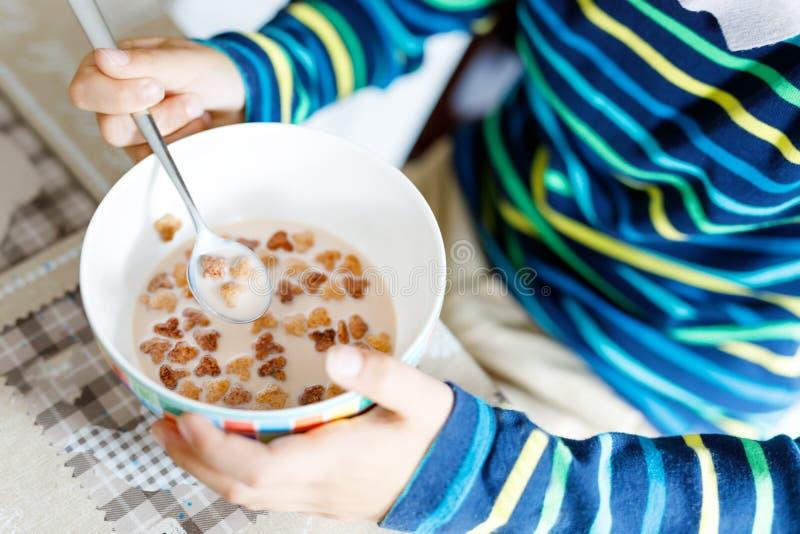 Nahaufnahme von den Händen des Kinderjungen selbst gemachte Getreide für Frühstück oder das Mittagessen essend lizenzfreie stockfotografie
