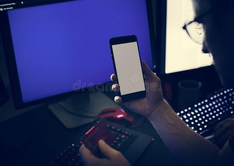 Nahaufnahme von den Händen, die Handy mit Computer halten stockbilder