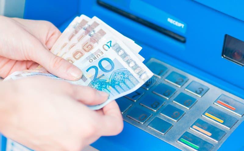 Nahaufnahme von den Händen, welche die Eurorechnungen zurückgenommen von ATM zählen stockfoto